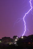 Lightning bolt by purple night sky. A thunderbolt hits the hill of a residential area - coloring the night sky into purple Stock Images