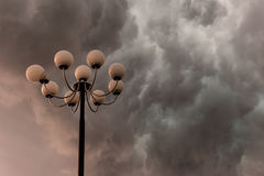 Lightning flashes stormy clouds over big, glorious street lamp Royalty Free Stock Image