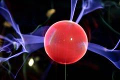Lightning meeting electrode in the plasma lamp, glowing red. Close-up of a lightning meeting electrode in a plasma lamp Tesla ball, glowing red royalty free stock photo