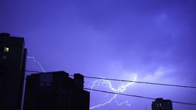 Lightning in the night sky in the city, a bright flash of light in the clouds in the rain, a thunderstorm. Thunderclouds stock footage