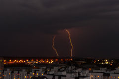 Lightning in the night sky over the city houses Royalty Free Stock Photo