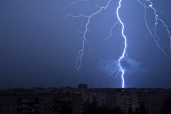 Lightning in the night sky strikes the roof of the house Royalty Free Stock Photo