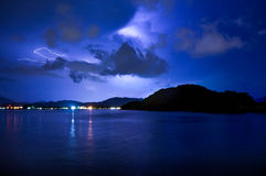 Lightning over calm sea and a mountain. Lightning over a calm sea, dark clouds and an island. Distant lights form a city are also visible in this night shot Stock Photo