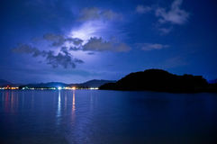 Lightning over calm sea and a mountain. Lightning over a calm sea, dark clouds and an island. Distant lights form a city are also visible in this night shot Royalty Free Stock Photos