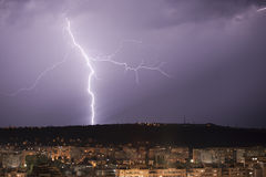 Lightning over city. And storm clouds Stock Images