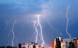 Lightning over the city. Lightning crackles over the buildings in a city Stock Photo