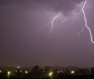 Lightning over city. And dark sky Stock Image