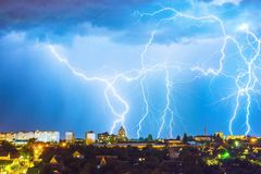 Lightning over the city in the night sky strikes the roof of the house.  Royalty Free Stock Photo