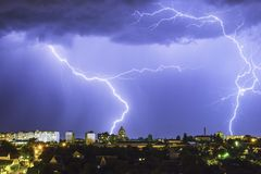 Lightning over the city in the night sky strikes the roof of the house.  Stock Images