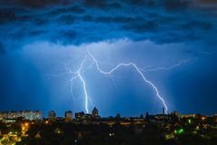 Lightning over the city in the night sky strikes the roof of the house.  Royalty Free Stock Photos