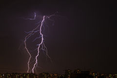Lightning over the city. During a night storm Stock Photos