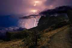 Lightning over the Karadag mountain range, Eastern Crimea. Lightning sparkle in the sky among the clouds, over the rocks of the black Sea coast, near Feodosia royalty free stock images