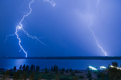 Lightning over the river Stock Images