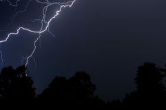 Lightning over the trees. In a black sky Stock Photos