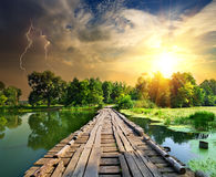Lightning over the wooden bridge. Lightning over a wooden bridge on a river Royalty Free Stock Photography