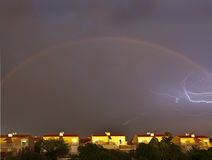 Lightning and Rainbow. Lightning inside the arc of a rainbow, over some residential houses Stock Images