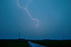 Lightning and road. Bright lightning in thunderstorms and road Stock Photos
