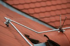 Lightning rod on a tiled roof. Closeup of a lightning safety rod conductor on a tiled roof Royalty Free Stock Photos