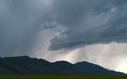 Lightning shoots out from thunder storm clouds over Idaho plains. Lightning bolts shoot out of dark gray clouds of thunder electrical storm over grassy plains in Stock Photos