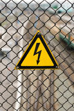 Lightning sign. Electricity danger sign on steel grid Stock Images
