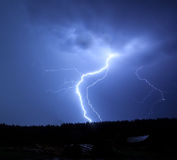 Lightning in sky on the background of trees Royalty Free Stock Photos