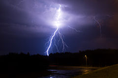 Lightning in the sky. Over the forest and the road stock photography