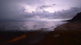 Lightning storm at night along beach shoreline. Thunderstorm and lightning flashes along coastline waterfront stock footage
