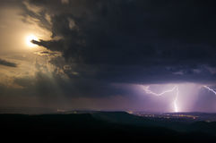 Lightning storm at night with full moon Royalty Free Stock Image