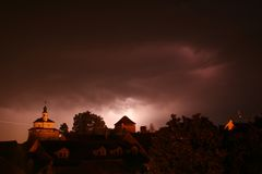 Lightning in a storm in old medival city with castle and a chapel (Kamnik, Slovenia) Stock Photos