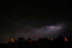 Lightning in a storm in old medival city with castle and a chapel (Kamnik, Slovenia) Royalty Free Stock Photo
