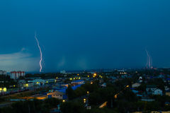 Lightning storm over city in blue light Royalty Free Stock Image