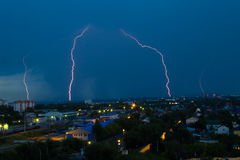 Lightning storm over city in blue light Royalty Free Stock Images