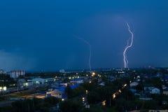 Lightning storm over city in blue light Stock Photo