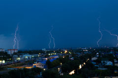 Lightning storm over city in blue light Royalty Free Stock Photo