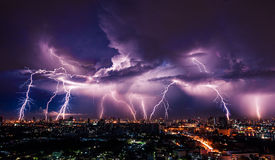 Lightning storm over city. In purple light royalty free stock image