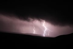 Lightning strike. In the darkness over mountains Stock Photos