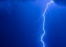 Lightning Strike. Photo of a lightning during a thunder-storm on a background of the dark dark blue sky Stock Image