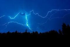 Lightning strike on a dark blue sky. Over the forest silhouette stock photo