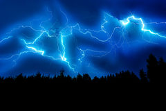 Lightning strike on a dark blue sky. Over the forest silhouette Stock Photography