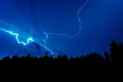 Lightning strike on a dark blue sky. Over the forest silhouette Stock Images