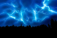 Lightning strike on a dark blue sky. Over the forest silhouette Royalty Free Stock Photos