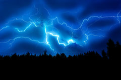 Lightning strike on a dark blue sky. Over the forest silhouette Royalty Free Stock Images