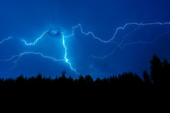 Lightning strike on a dark blue sky. Over the forest silhouette Stock Photos