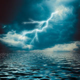 Lightning strike on the dark cloudy sky. Over the sea Stock Image