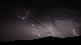Lightning strike over mountain range with clouds Stock Image