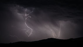 Lightning strike over mountain range with clouds Stock Photos