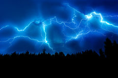 Lightning strike on sky. Lightning strike on a dark blue sky over the forest silhouette stock image