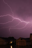 Lightning strike spanning the sky. Lightning bolt striking in the sky from clouds stock photography