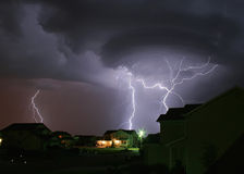 Lightning Strikes House. Thunderstorm producing a lightning bolt that strikes a house in a urban neighborhood Stock Photo