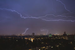 Lightning strikes over night town during a Stock Photos